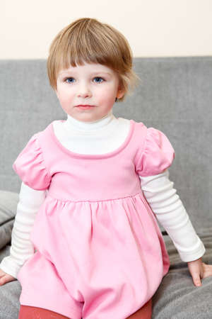 Portrait of small girl in pink dress sitting on couch and looking photo
