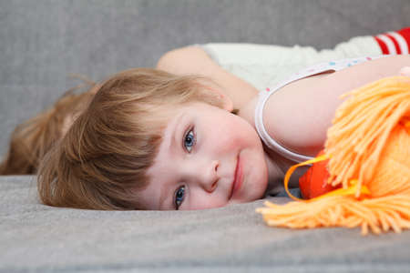 Small girl sleeping with doll toy on couch. Close up portrait photo