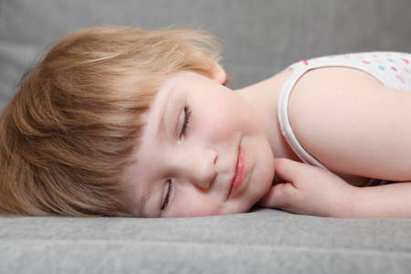 Small Caucasian girl sleeping on couch. Close up portrait