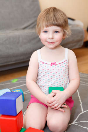 Portrait of small girl playing with bricks on floor photo
