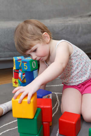 playing on divan: Portrait of small girl playing with bricks on floor