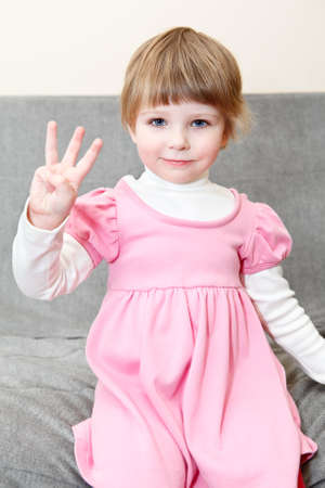 three persons: Portrait of small girl in pink dress showing three fingers on hand Stock Photo