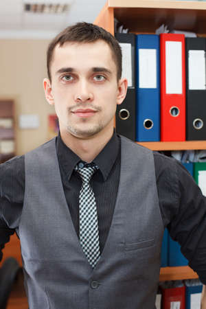 Handsome male business executive sitting behind a bookstand photo