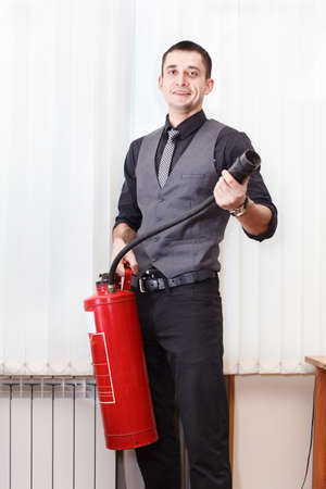 White collar worker with fire-extinguisher in office room photo