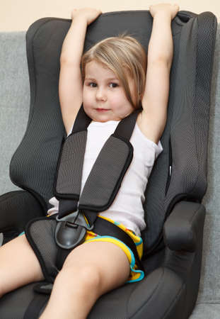 vehicle seat: Small girl sitting in a car safety seat with seatbelt Stock Photo