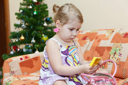 three year old: Small smiling girl sitting on couch with a christmas tree behind