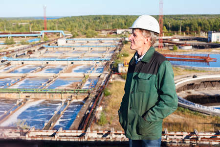 Mature man manual worker in white hardhat near sewage treatment plant photo