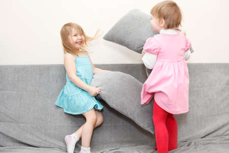 Two Caucasian happy playful little girls in pillows fighting on sofa photo