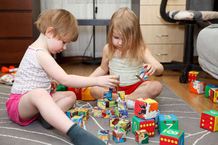 playing on divan: Small girls playing with bricks on floor at domestic room