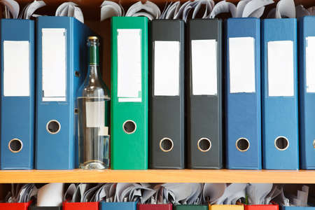 catalogues: Glass bottle with alcohol hidden between file binders on shelves