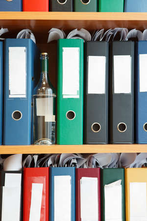 Glass bottle with alcohol hidden between file binders on shelves photo