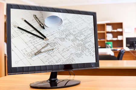 Computer monitor with blueprints and drawing tools picture in screen on desktop photo