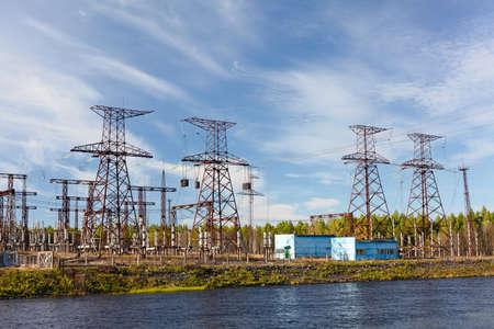 hoogspanningsmasten: De transmissie van elektriciteit op waterkrachtcentrale op blauwe hemel
