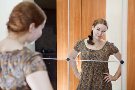 rear view mirror: Portrait of young Caucasian female in dress standing against mirror and looking at herself in domestic room Stock Photo