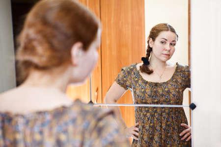 Portret van jonge blanke vrouw in jurk staande tegen de spiegel en kijken naar zichzelf in de binnenlandse kamer