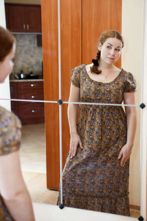 Portrait of young Caucasian female in dress standing against mirror and looking at herself in domestic room photo
