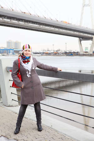 Portrait of happy young Caucasian female with red bag standing on embankment  Full length  Bridge on background