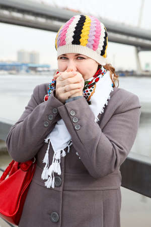 Portrait of frozen young Caucasian female warming hands and standing on embankment   Bridge on background photo