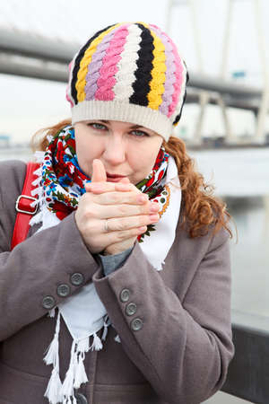 Portrait of frozen young Caucasian female warming hands and standing on embankment  Close up  Bridge on background photo