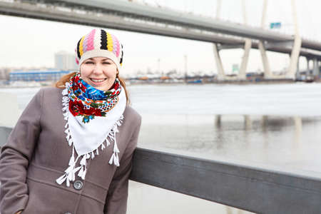 Portrait of happy young Caucasian female with scarf standing on embankment  Copy space photo