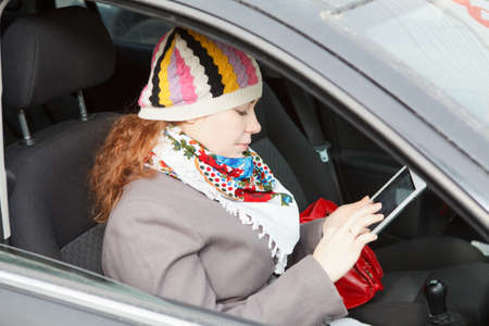 Young Caucasian woman sitting in car on passenger seat and holding electronic device photo