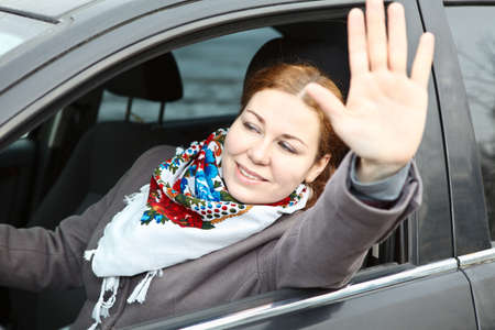 Pretty young Caucasian woman waving hers hand sitting in car photo