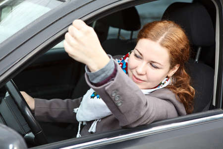 Pretty young Caucasian woman shaking hers fist sitting in car photo