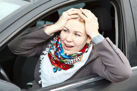 Pretty young expression Caucasian woman holding head by hands sitting in car photo