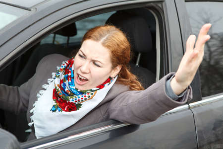 Pretty young Caucasian woman shaking hers hand and screaming sitting in car photo