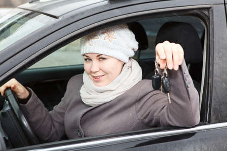 Young woman sitting in car and holding ignition keys in hand Stock Photo - 13143331