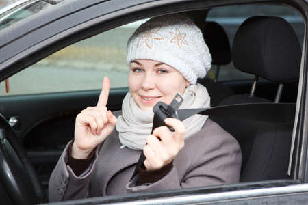 Young woman sitting in car and holding seat belt in hand photo