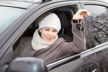 Young woman sitting in car and holding ignition keys in hand Stock Photo - 13817555