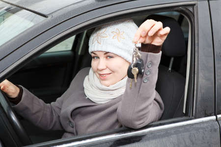 Young woman sitting in car and holding ignition keys in hand photo