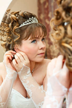 Beauty young Caucasian bride with curly hair looking in mirror and wearing earrings photo