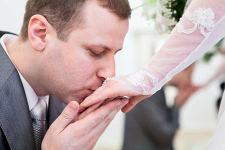 Young wedding Caucasian Russian couple  Groom kissing hand of bride photo