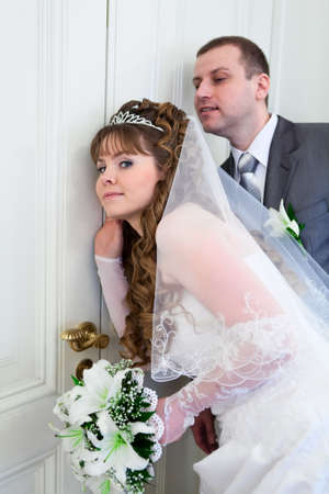 Young wedding Caucasian Russian couple hearing near closed doors Stock Photo - 13817579