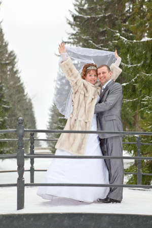 Young wedding Caucasian Russian couple standing on bridge in snowy park. Winter season in Russia photo