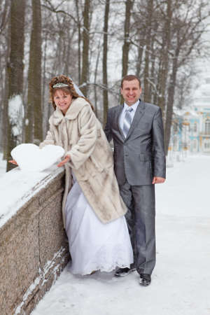Young wedding Caucasian Russian couple holding a snowy heart on bridge. Winter season in Russia photo