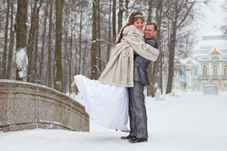 winter wedding: Young wedding Caucasian Russian couple embracing on snowy park. Winter season in Russia Stock Photo