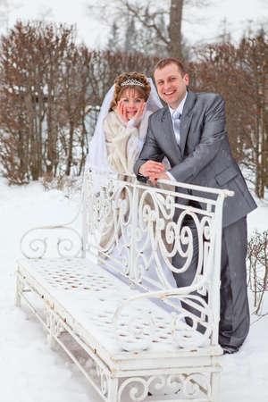 Young wedding Caucasian Russian couple walking on snowy park. Winter season in Russia photo