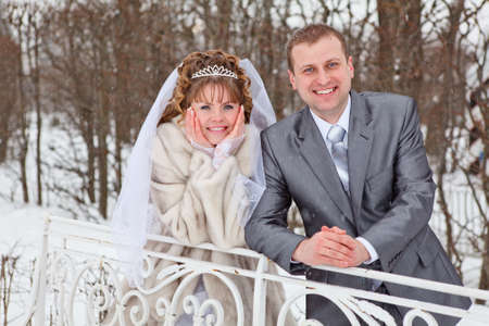 Young wedding Caucasian Russian couple walking on snowy park. Winter season in Russia photo