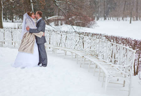 russian tradition: Young wedding Caucasian Russian couple kissing in snowy park. Winter season in Russia