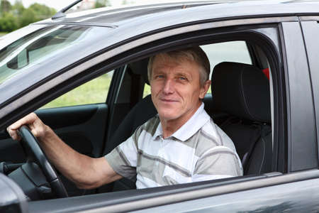 Happy senior person sitting in car on driver seat