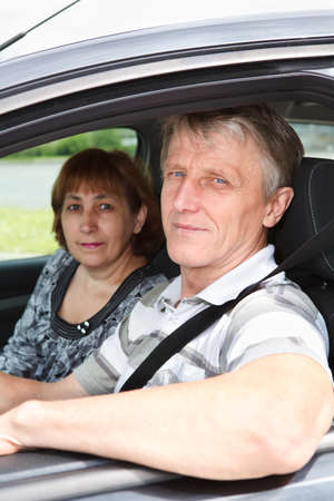 domestic car: Close up of senior Caucasian couple sitting in domestic car and smiling