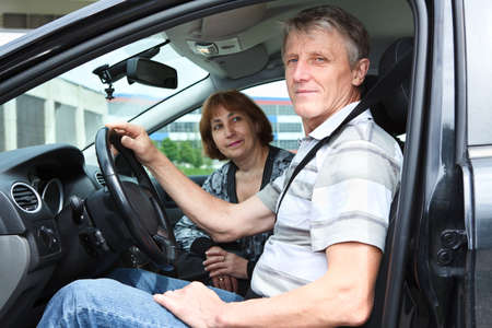 Senior Caucasian man and woman in domestic car smiling photo