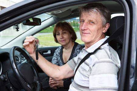 Senior Caucasian male and woman sitting in new car and holding ignition key photo