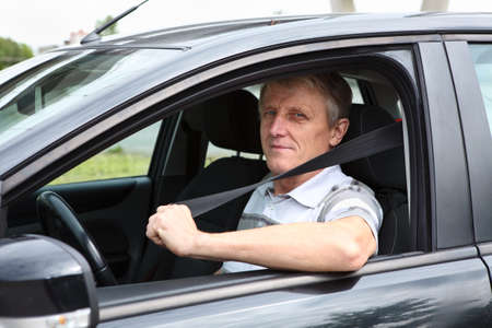 Smiling Caucasian senior male fastens safety belt sitting in car on driver seat Stock Photo - 14127084