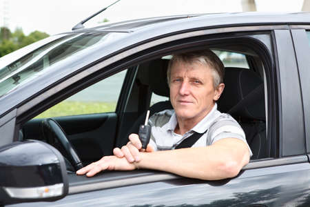 Senior male sitting in car on driver seat and holding ignition key Stock Photo - 14127095