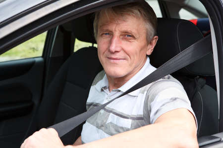 Handsome mature male fastens safety belt sitting in car on driver seat Stock Photo - 14127096