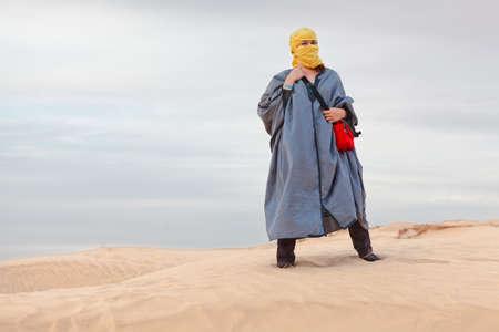Female in bedouin clothes standing on dune in desert photo